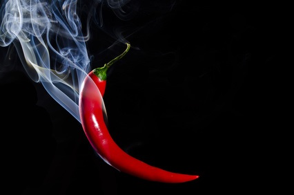 Smoking red hot chili pepper on black background