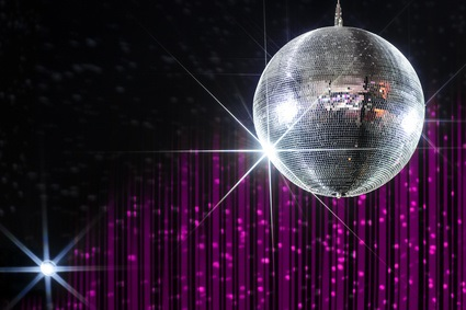 Disco ball with stars in nightclub with striped pink and black walls lit by spotlight